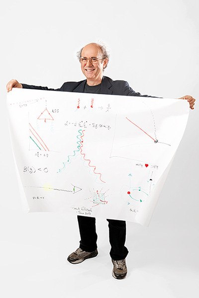 A man standing, holding a large piece of paper with diagrams drawn in crayon.